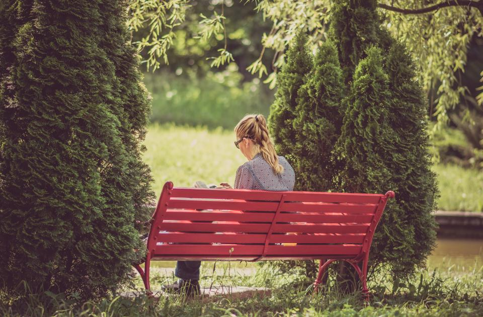 Image of a lady sitting on a peaceful park bench